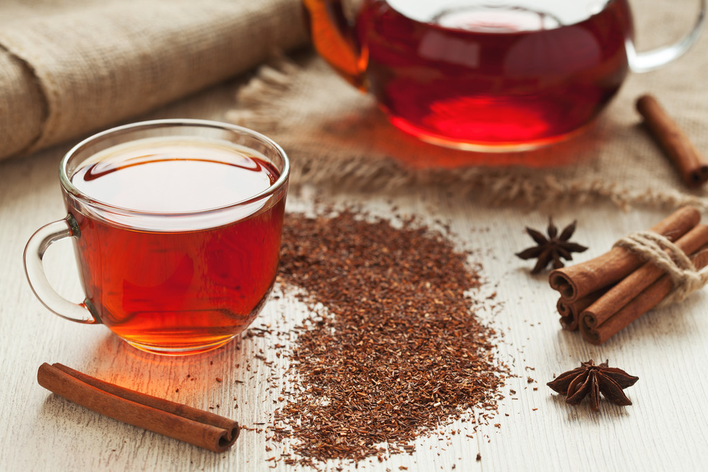 Traditional healthy red african rooibos tea in glass cup with spices on vintage table background